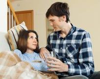 Homme affectueux s'occupant de l'amie malade Image libre de droits