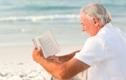 Homme affichant un livre sur la plage Images libres de droits