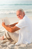 Homme affichant un livre sur la plage Image stock