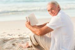 Homme affichant un livre sur la plage Photos stock