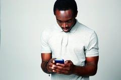 Homme africain étonné à l'aide du smartphone Photos libres de droits