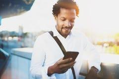 Homme africain américain de sourire à l'aide du smartphone pour appeler ses amis à la ville ensoleillée tandis que son frein Conc Photos libres de droits