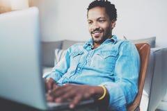 Homme africain barbu de sourire faisant la conversation visuelle par l'intermédiaire de l'ordinateur portable avec des amis tout  Photos libres de droits