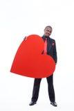 Homme africain dans la suite tenant le grand coeur rouge Photographie stock libre de droits