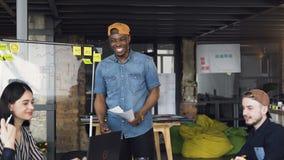 Homme africain de hippie présent le résultat du nouveau plan d'action au cowoker au cours de la réunion d'affaires dans le bureau banque de vidéos