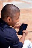 Homme africain de sourire à l'aide du comprimé numérique dehors photographie stock