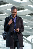 Homme africain de sourire d'affaires marchant avec le téléphone portable et le sac Photo stock