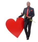 Homme africain de sourire jugeant la rose de rouge disponible Image stock