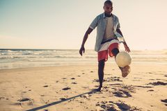 Homme africain jouant avec du ballon de football à la plage Photos libres de droits