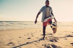 Homme africain jouant avec du ballon de football à la plage Photographie stock libre de droits