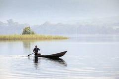 Homme africain montant un canoë image stock