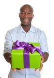 Homme africain riant montrant un cadeau pour Noël Photo stock