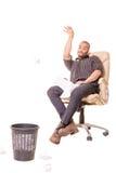 Homme africain s'asseyant dans la chaise et jouant le basket-ball avec des déchets Photographie stock