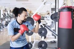 Homme africain s'exerçant avec un sac de boxe Photographie stock