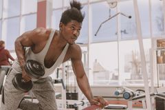 Homme africain sportif ?tablissant avec des halt?res au gymnase photographie stock
