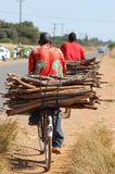 Homme africain transportant le bois Image stock
