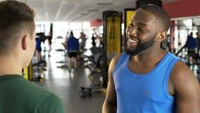 Homme afro-américain de sourire parlant avec l'instructeur de forme physique au gymnase, sport banque de vidéos