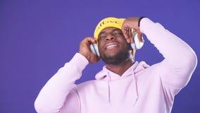 Homme afro-américain mignon dans des écouteurs habillés dans l'usage de style de rue, écoutant la musique banque de vidéos