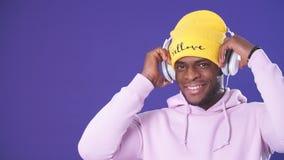 Homme afro-américain mignon dans des écouteurs habillés dans l'usage de style de rue, écoutant la musique clips vidéos