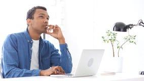 Homme afro-américain pensant et travaillant dans son bureau photo libre de droits