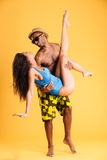 Homme afro-américain tenant son amie avec deux mains Photographie stock