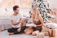 Homme agréable bel donnant un cadeau de Noël à son amie Image stock