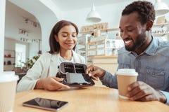 Homme agréable enlevant le téléphone de son casque des amis VR Photographie stock