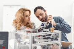 Homme agréable enseignant à son collègue comment utiliser l'imprimante 3D Images libres de droits