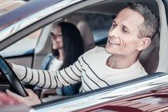 Homme agréable gai regardant hors de la fenêtre de voiture Image libre de droits