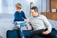 Homme agréable observant son fils dessiner en dessin-livre Photographie stock libre de droits
