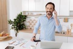Homme agréable parlant au téléphone dans la cuisine Photographie stock libre de droits