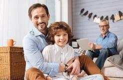 Homme agréable positif étreignant son fils Images stock