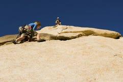 Homme aidant la roche s'élevante d'ami contre le ciel bleu Images stock