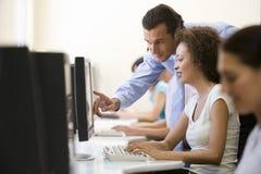Homme aidant le femme dans la salle des ordinateurs Photographie stock libre de droits