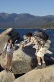 Homme aidant son amie dans les roches s'élevantes Photographie stock libre de droits