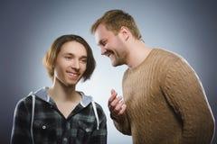 Homme aimable parlant à un adolescent heureux sur le fond gris téléphone noir de récepteur de concept de transmission Image libre de droits