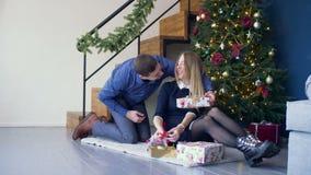 Homme aimant étonnant sa femme avec le cadeau de Noël banque de vidéos