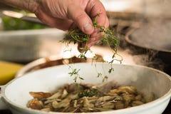 Homme ajoutant l'herbe de thym au plat de shiitaké Image libre de droits