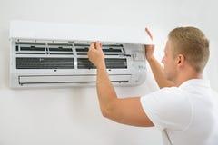 Homme ajustant le dispositif de climatisation Photos libres de droits