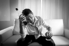 Homme alcoolique d'affaires gaspillé dans le lien lâche bu avec la bouteille de whiskey sur le divan Images stock