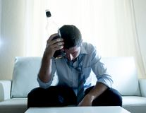 Homme alcoolique d'affaires portant la cravatte lâche bleue bue avec la bouteille de whiskey sur le divan Photo stock