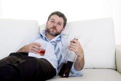 Homme alcoolique d'affaires portant la cravatte lâche bleue bue avec la bouteille de whiskey sur le divan Images stock