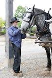Homme amish préparant son cheval pour le travail à la journée Photo libre de droits