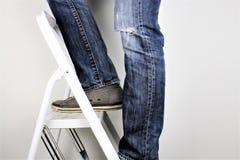 Homme anonyme atteignant sur l'échelle s'élevant, à l'intérieur tir de personnes de studio Image libre de droits
