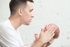 Homme apaisant un nouveau-né criard Image stock