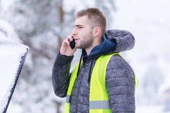Homme appelle des services de voiture d'hiver pour aider image stock