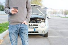 Homme appelle le mécanicien après panne de voiture photos stock
