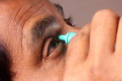 Homme appliquant la goutte pour les yeux Photographie stock libre de droits