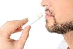 Homme appliquant le baume à lèvres hygiénique photos libres de droits