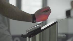 Homme appliquant le bracelet de RFID à l'équipement électronique d'accès sur la porte d'entrée au souterrain, au souterrain ou au banque de vidéos